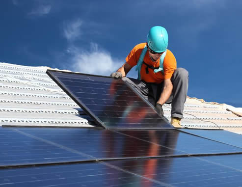 Photo of worker installing solar panels